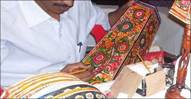 A craftman working on a piece of wooden handicraft